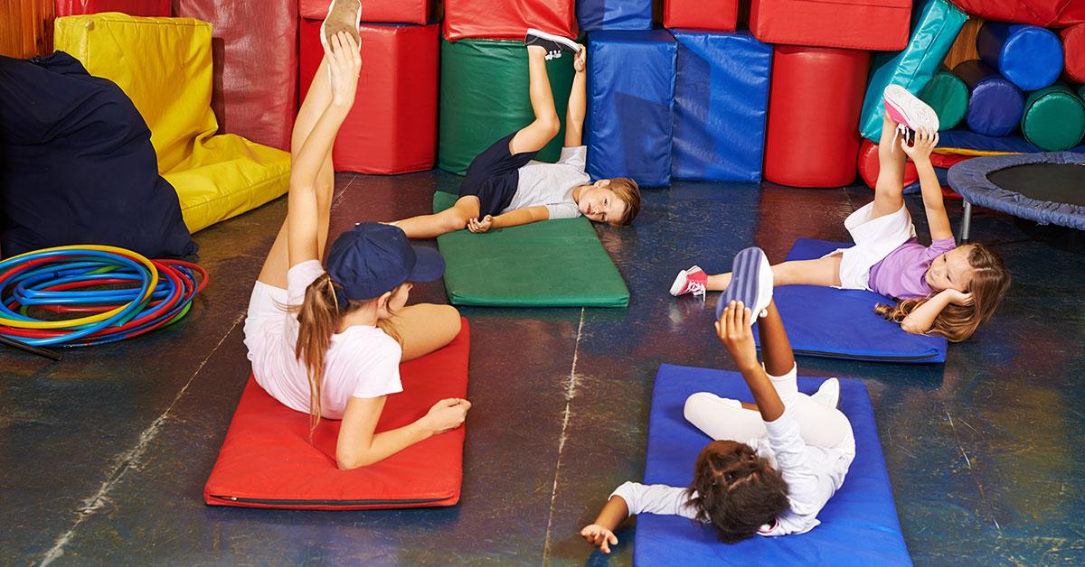 Nenes elongando las piernas con maetra