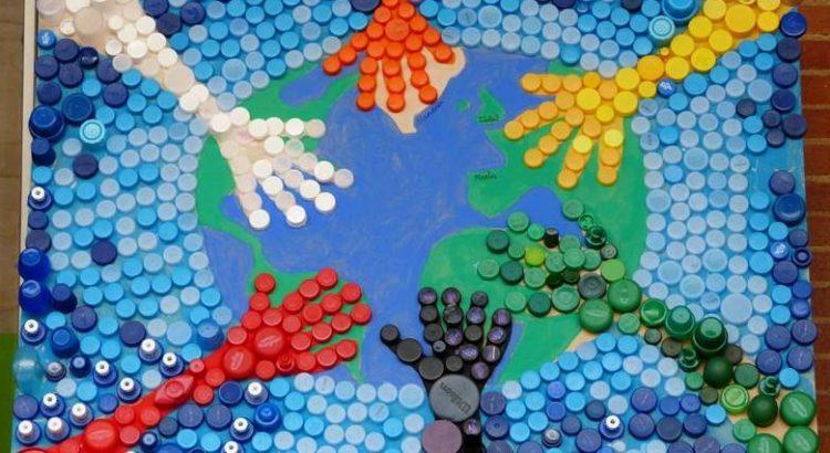 Manos abrazando el planeta realizadas con tapitas
